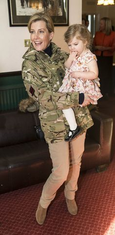 Sophie, Countess of Wessex wore a pair of sand colored trousers which complemented her camouflage military style jacket worn especially for the occasion this afternoon.  The Royal seen scooping up Fiona Cox's daughter Thalia during her visit to the Corporals mess at Ward Barracks, Bulford on 11 January 2017