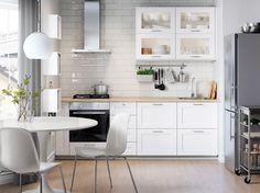 Fehér konyha rozsdamentes háztratási eszközökkel, fehér székkel és kör alakú asztallal.