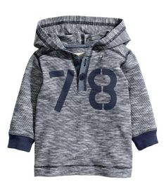 Hooded shirt in cotton fabric with a printed design at front, buttons at top, and rib-knit trim at cuffs.