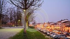 Illuminated pathway and lots of cars parked along the street in Treviso, north Italy, Europe.