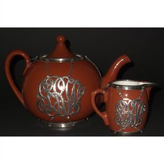 This antique Villeroy & Boch teapot with sterling silver overlay also includes a matching creamer. It's an elegant example of Art Nouveau pottery produced with an elaborate decorative motif in sterling silver overlay. The exterior is dark brown; the interior is in white porcelain; the rim, base and decorative overlay are marked sterling silver. The mark on the base indicates that they were produced between 1874-1909 in Luxemburg, at the height of the Art Nouveau movement in Europe.