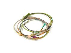 Sophisticated and delicate gold plated bangle bracelets with silk and charms. Get yours on www.sophisticatedgold.nl