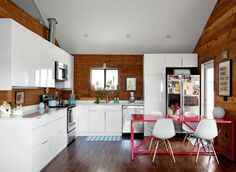 Blu Dot Strut Table. Modern Green Neighborhood = SOL Austin - Photo from the New York Times - Development and Construction by General Contractor Beck-Reit and Sons - Modern Kitchen - reclaimed wood, white cabinets