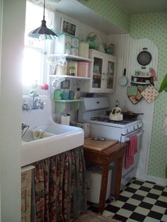 Love this retro tiny kitchen with checkerboard floor, gas range, and all the retro details. | Tiny backyard garden cottage. Photos by Robin Lake.