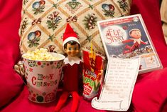 """December 2 – The kids woke up to find Buddy watching his own movie, snacking on popcorn and juice. He even signed the DVD case for them.""  So cute!"