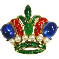 This charming signed Trifari pin is a miniature work of art; it features metallic red and green enamel accented with open backed green and blue art