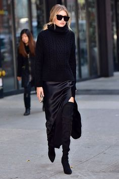 All in black: turtleneck sweater, silk maxi skirt and over-the-knee boots.