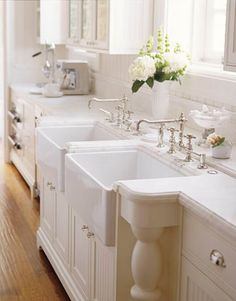 """Twin Farmhouse Sinks  These pristine farmhouse sinks and Julia faucets are from Waterworks. """"I like two sinks side by side,"""" says the house's owner and designer, Susan Dossetter. """"One becomes a receptacle for dirty pots and pans while you keep working in the other, and I love the fact that it's so deep you can't see the dirty dishes from across the room."""" Double Farmhouse Sink, Farmhouse Sinks, White Farmhouse, Farmhouse Style, French Farmhouse, White Cottage, Farmhouse Addition, Southern Cottage, Farmhouse Kitchens"""