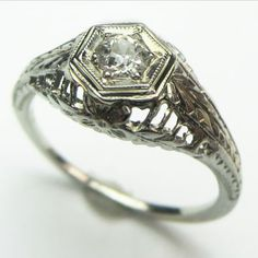 Delicate Flower: A charming little ring with dimensional filigree, a bright white antique diamond, and a lovely engraved flower tucked into the undergallery. Ca.1930.  Maloys.com