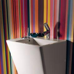 El baño es muy particular porque hay las paredes con rayas verticales colores. En el baño está un lavabo blanco.