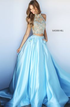 Beaded appliques adorn the illusion halter crop top with a sweetheart lining and a semi-open back of this full-length Sherri Hill 51041 two-piece prom dress. The box pleated ball gown skirt with a sweep train showcases a beaded waistband and beaded appliques accent the side pockets.
