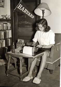 """Among books and notes, a Vassar student studies at her typewriter in her dorm room, 1950's.© Vassar College, Archives & Special Collections. """"College is a place to keep warm between high school and an early marriage."""" — George Gobel."""