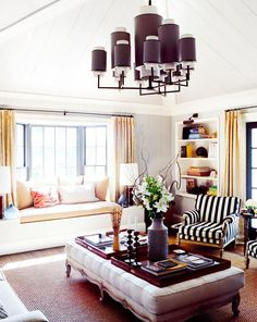 Warm living space with striped armchair, modern light fixture, and love seat in window