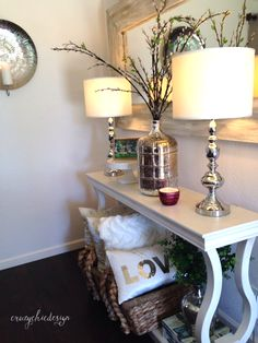 Styling a Console Table: Create height and balance with lamps, a large vase, and accessories in between. Add storage with a large basket for pillows and blankets. HomeGoods Sponsored Pin.