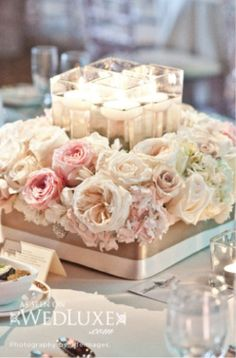 Wedding Centerpiece--Such an elegant look, easily done with any four candles are flowers. Simply use a styrofoam wreath base to put all the flowers in around the candles!