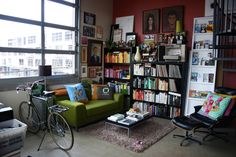 i see myself in the styling of this living room...love the green couch and collections of books arranged by color