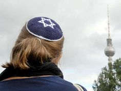 """German Jews 'no longer safe' due to anti-Semitism and 'deteriorating security' and Germany welcoming of refugees brought up in cultures """"steeped in hatred"""" for Jews were resulting in anti-Semitism. A woman wears a kippah, the traditional Jewish headdress, as she takes part in a demonstration in Berlin (Picture: [copyright])"""