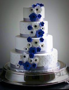 Quilted fondant with hand-made flowers and a silver ribbon at the base of each tier.