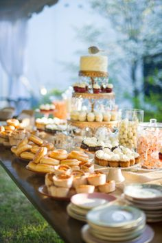This outdoor dessert table display is so inviting - cakes, cupcakes, donuts, muffins and more! #gardenparty #gardenpartywedding #desserttable #dessert #outdoorwedding