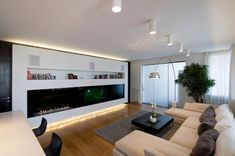 Perfect Living Room Design with Wooden Flooring and White Wall Paint Color and Wall Units using Black Screen TV LCD Idea and Bookcase Idea and U Shaped Cream Fabric Sectional Sofa Set feat Black Fabric Pillows Idea and Rectangular Shaped Black Wooden Coffee Table