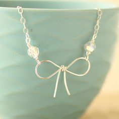 """Tie the Knot Sterling Silver and Swarovski Crystal Bow Necklace Beautiful and delicate hand formed sterling silver bow pendant necklace with Swarovski crystal and finished with a sterling silver chain. Bow measures approximately 1 1/4"""" x 3/4"""". Contact me for special discount pricing for bridal parties ordering 3 or more pieces of jewelry."""