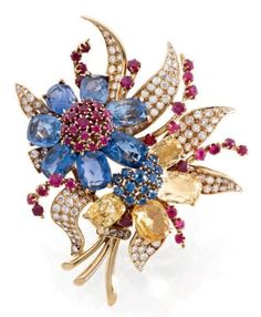 "VAN CLEEF & ARPELS Clip ""flowers"" made ​​of yellow gold set with sapphires two flowers blue and yellow cushion cut, rubies, leaves fully paved with brilliant-cut diamonds accented with branches set with rubies. Signed and numbered. 1939"