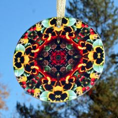 Glass suncatcher adorned with my red pansy and yellow pansy boho chic mandala new age sacred geometry kaleidoscope design tilted Minutia <br /> <br />This stunning pansy glass suncatcher illuminates my geometric mandala kaleidoscope design when light shines through it! It is 3 - ½ inches in diameter and has a beveled edge. The suncatcher comes with a ribbon ...