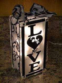 Made from a frosted glass block filled with lights (found at large craft stores like Hobby Lobby) and decorated with stickers or stencils and ribbon.  Lovely!