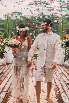 """Para abençoar sua união com o DJ Alok, Romana Novais escolheu um vestido de noiva moderno. De pés descalços, ela usou um modelo branco inteiramente bordado, com decote em V e babados, assinado pelo Atelier Le Lis Blanc. Para completar o look, uma coroa de flores da espécie jasmim-manga. """"Ela mesma teve a ideia e escolheu a espécie que brota e floresce mesmo sem raízes, por isso traz o significado da imortalidade da alma e do amor"""". Casamento, cerimônia intima, Bali, Indonésia;  Second Wedding Dresses, Wedding Dress Men, Elope Wedding, Dream Wedding, Wedding Day, Beach Wedding Groom Attire, Groom Looks, Alternative Wedding, Poses"""