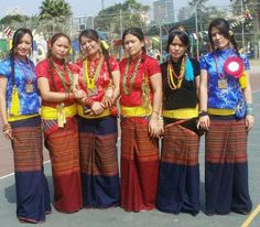 Nepal The Tamangs. Tamang women wear red or black coloured blouses and blue with red horizontal patterns saris wrapped around the waist and supplemented by yellow patuka. Men and women wear a special kind of woolen cap.