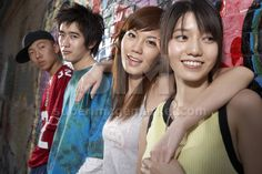 Chinese teenagers leaning on wall of graffiti