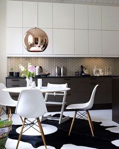 interior design mid century modern kitchen with dark grey charcoal and white cabinet doors, black hide rug, white tulip breakfast table, white baby high chair, tom dixon pendant light