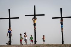 Children play along the site of the re-enactment of the crucifixion of Jesus Christ on Holy Wednesday in Cutud village, City of San Fernando in Pampanga. On Good Friday, more than tourist. Crucifixion Of Jesus, Jesus Christ, Holy Wednesday, Good Friday, Photojournalism, Kids Playing, Children Play, San, City