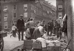 Street Scene in the Jewish Quarter. On the bridge to Uilenburg women search between rags and clothes. Amsterdam, 1910