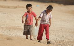 Two Syrian boys in Jordan's Zaatari refugee camp help each other to carry water back to their tent.