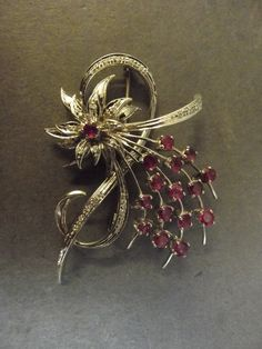 "A white gold, ruby and diamond set floral spray brooch, 2"" w"