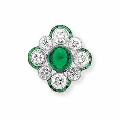 Cabochon Emerald and Diamond Ring Platinum, centering one oval cabochon emerald approximately 1.70 cts., encircled by 8 old European-cut diamonds approximately 3.20 cts., quartered by 4 slender curved bands set with numerous calibre-cut emeralds, circa 1920