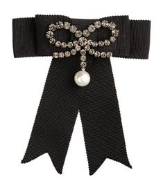 Black. ERDEM x H&M. Metal clip brooch with a grosgrain bow decorated with a smaller rhinestone bow with a pearlescent plastic bead. Length 4 1/4 in.