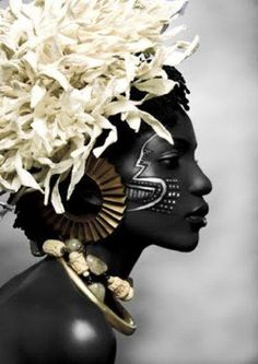 a beauitful black woman with constrasting white flowers in her hair -  Tropics Mag