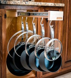 Pullout pot rack. Notice that each lid is slipped over its respective pot handle. This would not be a difficult DIY.