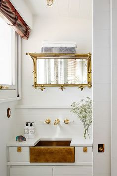 Small white and brass bathroom behind a pocket door.