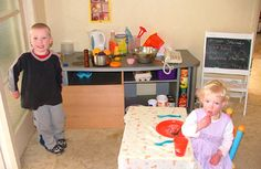 Homemade play kitchen, notice actual phone, real empty food containers, cans, etc.; re-use and play with actual materials, not replicas