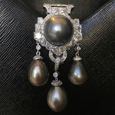 Wonderful natural grey pearl and diamond clip brooch by Cartier.
