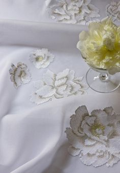WHITE PEONIES These exquisite bed linens show the light but authoritative hand of master artisans. Shown here on white organdy. Designed by Patricia Kha.