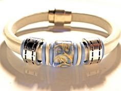 This unique original bracelet is made with authentic white Regaliz leather and centered in the middle is a gorgeous ceramic periwinkle blue biege and white slider bead that has a Leather Jewelry, Jewelry Box, Jewelry Bracelets, Jewelry Accessories, Jewelry Design, Jewelry Making, Bangles, Leather Braces, Cartier Love Bracelet