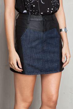 Saia de tecido semelhante à couro com recorte em jeans na parte da frente, bolsos frontais e posteriores e fechamento por zíper e botão na parte da frent