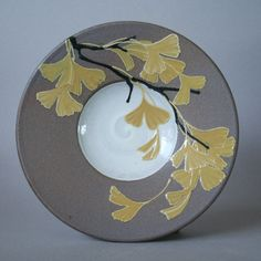 Hand-thrown stoneware plate decorated with vivid yellow autumn ginkgo leaves. This plate can be hung (wire hanger on back) but is also