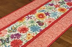Cheerful spring/summer table runner featuring spring flowers and butterflies in shades of red, aqua, gold and purple on a white background. The outer borders and binding are from the same fabric line and match the flowers perfectly. The backing fabric is a coordinating print from