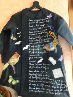 Black coat embroidered with words, birds, and butterflies
