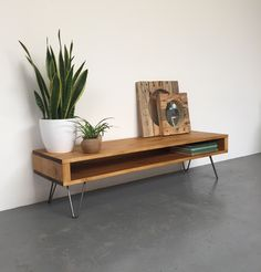This is a low version of our classic industrial rustic style TV console, media unit or coffee table. It is made from a high quality rustic softwood, sanded to a beautifully smooth finish, stained and treated with a hard wearing oil finish and wax. It is sat on 20cm high Eames style hairpin legs and measures 34cm (14) in total height. It has a full width, 9.5cm (3.7) high opening that is accessible from either side of the table, ideal for housing coffee table paraphenalia or a DVD player…